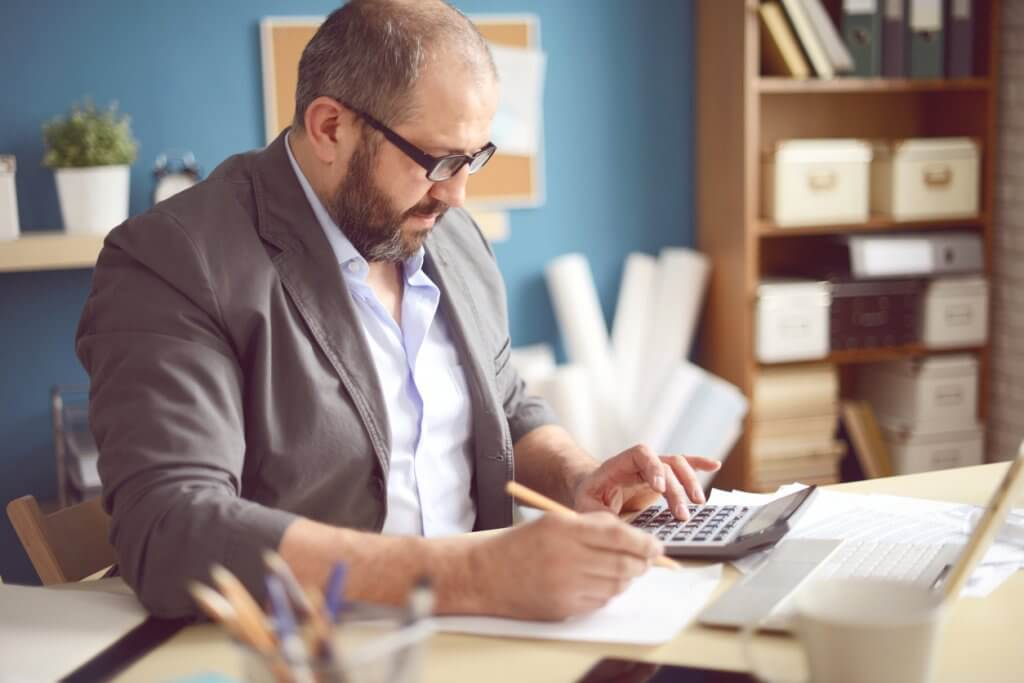 adult man creating business budget using calculator