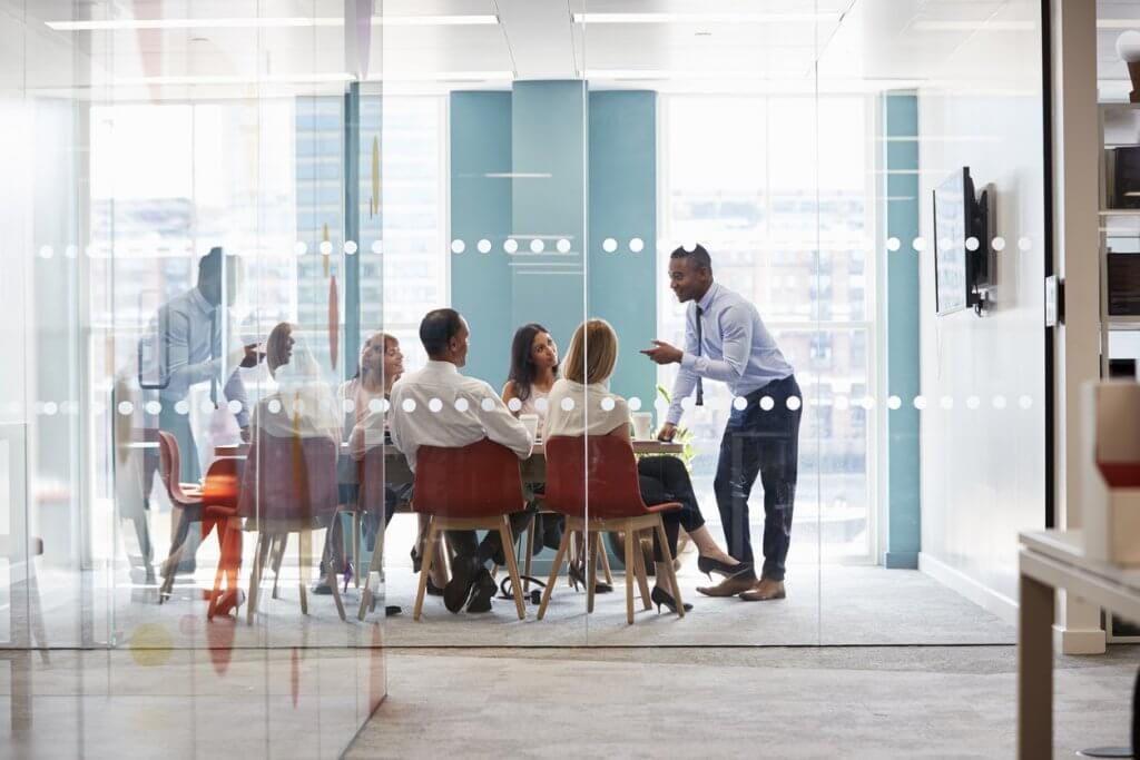 man-speaking-to-team-of-employees-seated-in-red-chairs-at-conference-table-in-room-with-glass-wall